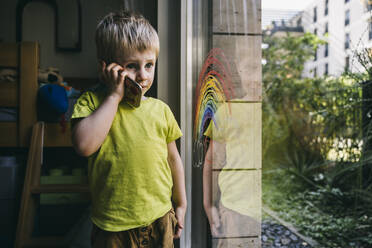 Portrait of little boy on the phone at home - MFF05421