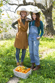Two women with their harvest of organic oranges and lemons - VSMF00043