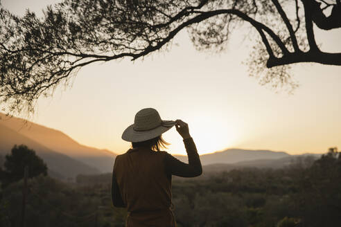 Woman enjoying the view of the sunset in the countryside, Orgiva, Andalusia, Spain - VSMF00064