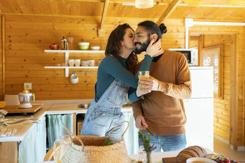 Young couple hugging and kissing in a wooden cabin - VSMF00085
