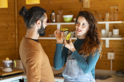 Young couple with avocados in a wooden cabin - VSMF00088