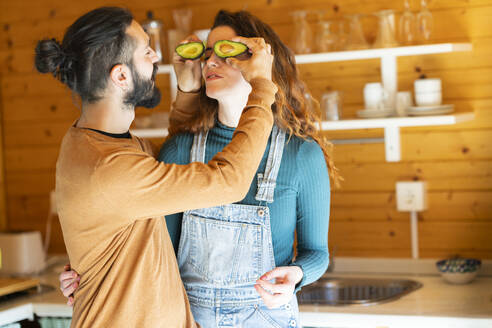 Playful young couple having fun with avocados in a wooden cabin - VSMF00091