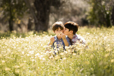 Mother kissing daughter in a field of wildflowers - VSMF00097