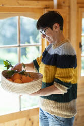 Woman with basket of oranges in a wooden cabin - VSMF00106