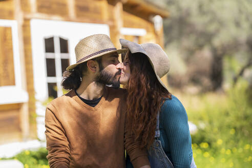 Young couple kissing in front of a wooden cabin - VSMF00112