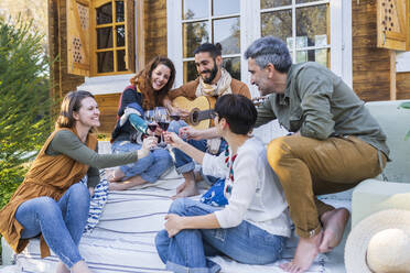 Friends playing music on the guitar and drinking wine outside a cabin in the countryside - VSMF00160