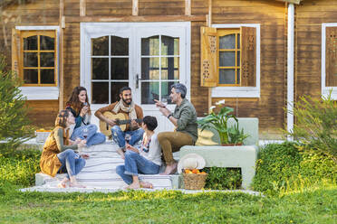 Friends playing music on the guitar and drinking wine outside a cabin in the countryside - VSMF00163