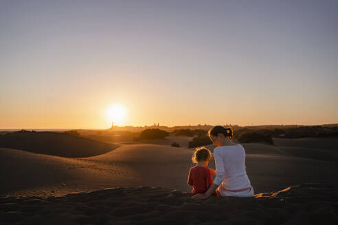 Mother and daughter sitting in sand dunes at sunset, Gran Canaria, Spain - DIGF09542
