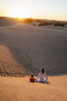 Mother and daughter relaxing in sand dunes at sunset, Gran Canaria, Spain - DIGF09551