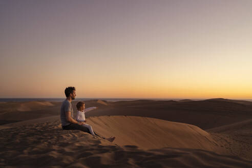 Father sitting with daughter in sand dunes at sunset, Gran Canaria, Spain - DIGF09560