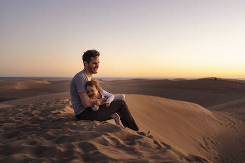 Happy father sitting with daughter in sand dunes at sunset, Gran Canaria, Spain - DIGF09563