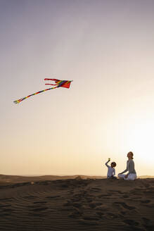 Mother and daughter flying kite in sand dunes at sunset, Gran Canaria, Spain - DIGF09590