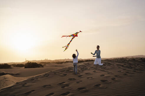 Mother and daughter flying kite in sand dunes at sunset, Gran Canaria, Spain - DIGF09596