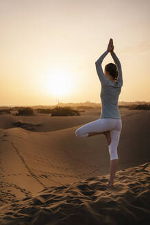 Woman practicing yoga in sand dunes at sunset, Gran Canaria, Spain - DIGF09611