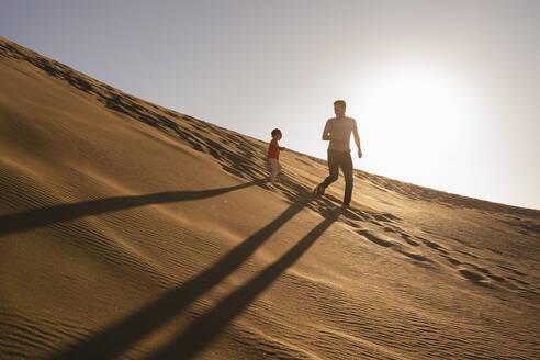 Father and daughter running in sand dune at sunset, Gran Canaria, Spain - DIGF09614
