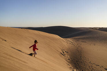 Girl running down sand dune, Gran Canaria, Spain - DIGF09626