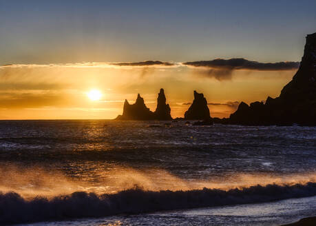 Iceland, Silhouettes of Reynisdrangar sea stacks at moody sunset - TOVF00156