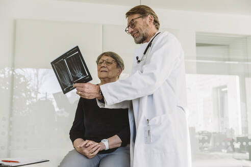 Doctor discussing x-ray image of broken hand with senior patient - MFF05434