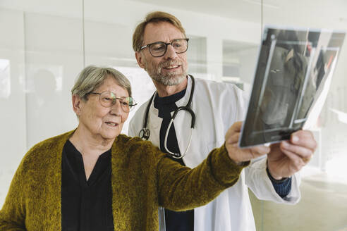 Doctor discussing x-ray image with senior patient - MFF05437