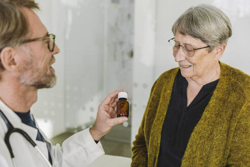 Doctor recommending pills in bottle to senior patient - MFF05446