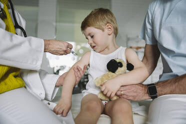 Pediatrist injecting vaccine into arm of unhappy toddler - MFF05524