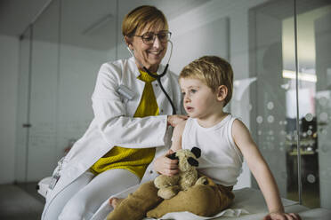 Doctor examining toddler boy with a stethoscope - MFF05530
