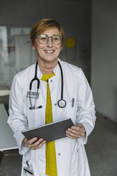Portrait of smiling doctor holding tablet - MFF05551