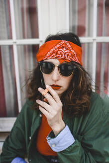 Portrait of young woman wearing headband and sunglasses smoking carrot - FVSF00074