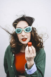 Portrait of woman wearing diving goggles eating strawberry - FVSF00077