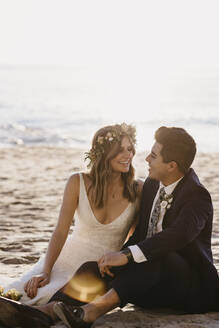 Happy bridal couple sitting at the beach - LHPF01258