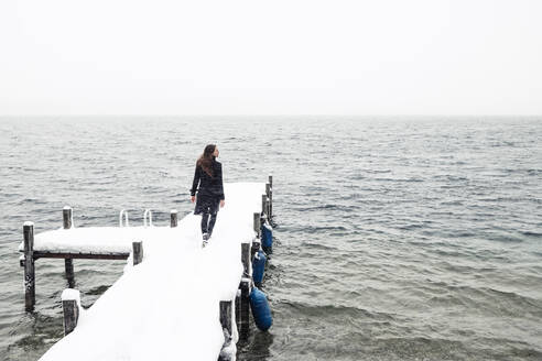 Back view of young woman walking on snow-covered jetty at Lake Starnberg, Germany - WFF00324