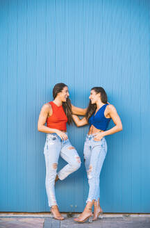Smiling twins leaning on blue wall - DAMF00319