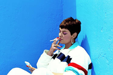 Woman wearing swag style smoking and checking her smartphone - ERRF03403