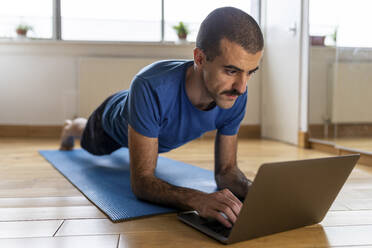 Man doing a plank and using laptop at home - WPEF02758