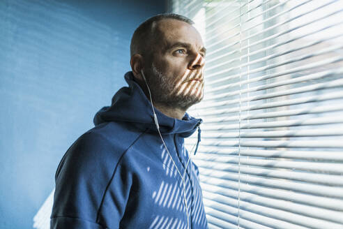 Pensive man with earbuds looking out of venetian blind window - MCVF00280