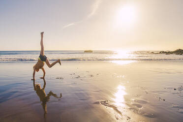 Little boy practicing handstand on the beach - IHF00321
