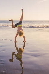 Little boy practicing handstand on the beach - IHF00324