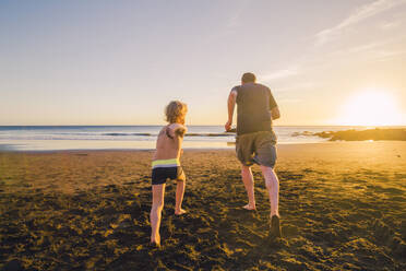Father and son running on the beach, rear view - IHF00327