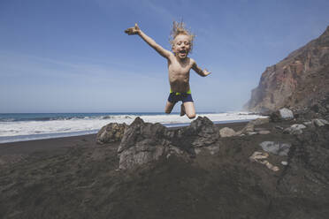 Little boy jumping for joy on a rocky beach - IHF00330