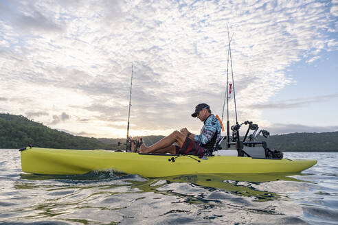 Man in a kayak fishing in the Pacific Ocean at sunrise, Costa Rica - AMUF00041
