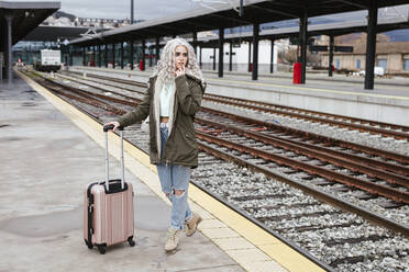 Portrait of young woman with rolling suitcase standing on platform - LJF01493