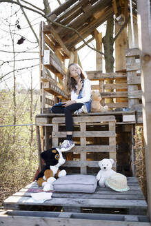 Thoughtful girl playing with her teddy bears at tree house - HMEF00882