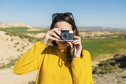 Woman taking pictures with a vintage camera, Bardenas Reales, Arguedas, Navarra, Spain - XLGF00002