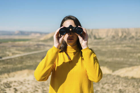 Portrait of a woman with binoculars, Bardenas Reales, Arguedas, Navarra, Spain - XLGF00011