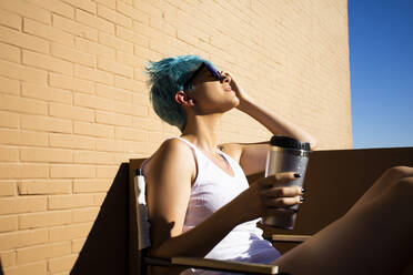 Young woman with blue hair pouring water over her head on balcony - ERRF03426
