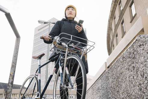 Woman with bicycle and smartphone in the city, Frankfurt, Germany - AHSF02216