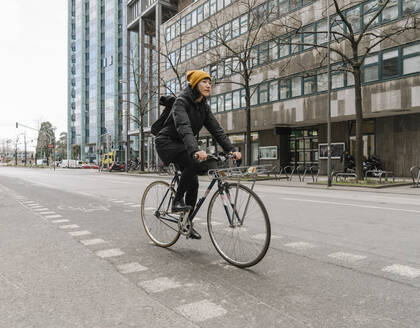 Woman riding bicycle in the city, Frankfurt, Germany - AHSF02219