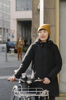 Portrait of confident woman with bicycle in the city, Frankfurt, Germany - AHSF02240