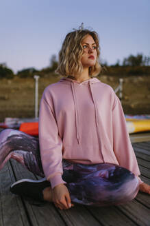 Portrait of young blond woman wearing pink hoodie sweater on jetty - AGGF00012