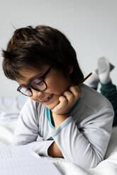Portrait of little boy lying on bed doing homework - VABF02770